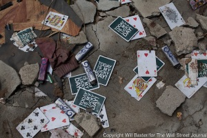 "Playing cards with the saying ""Today is my lucky day!"" written on them lie scattered about amongst lighters at a warehouse that held lighters and cigarettes in San Jose district, Tacloban, November 21, 2013. Photo by Will Baxter/for The Wall Street Journal"